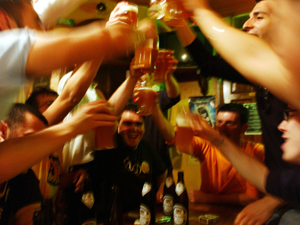 """STRASBOURG, FRANCE - MAY 18. Italian students from the Primo Levi Technical Institute of Vignola in the Modena Province, toast wit glasses of beer in a pub during a school trip to Strasbourg to visit the European Parliament on May 18, 2004. School trips for teenager are very often a sort of initiation trip where they get in contact for the first time with alcohol and drugs and were they never sleep for the all time of the trip. But they can be also extraordinary occasion to get to know each others better even if for those which are consider """"different"""" can be a nightmare experience .Mainly the teenager during those school trip are only interested in clubs, shopping and having a pizza instead that the cultural aspects of the tripp. (Photo by Marco Di Lauro/Getty Images)"""